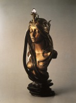 The bust of a woman with bare breasts, long and ondulating hair and a crown capped with a light fitting