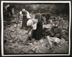 Three women and two men in traditional costume bent over a pile of rubble with pick-axes