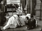 Mucha looks on as 4 women in traditional costume crouch down on the floor in a huddle and a 5th woman with a white headdress holds her arms up to the sky