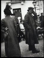 Woman seen from behind wearing a hat, a long coat and a handbag stood next to a beggar with his left hand to his cap and a frown on his face