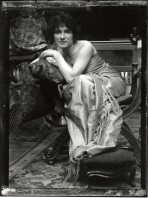 Bare-shouldered model sitting on an ornate wooden chair and leaning on a cushion placed on the right arm of the chair