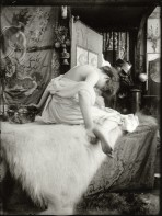 Bare-shouldered model sits on a white rug on a couch and leans forward away from the camera