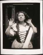 A Woman in a white dress with a laced up black bodice holds her hands out beside her face and looks upwards