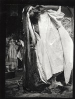 A bearded man in a white tunic and a fabric headdress touches his face with his left hand as he leans to his right