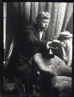 Model in a dark suit holding a top hat and leaning forward over an armchair with his right hand held out in front of him