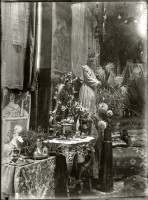 An interior with pictures on the wall, ornate furniture, cut flowers and objets d'art