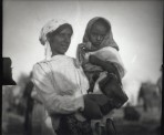 A dark-haired women with a white polka dot headdress holding a small child with a headdress