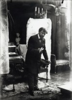 Mucha dressed in formal clothes holding a top hat and leaning forward with his left hand on a chair behind him