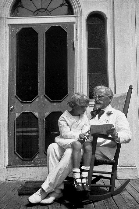 Mucha dressed in a white suit sitting on a rocking chair on a wooden veranda with his son Jiří on his knee