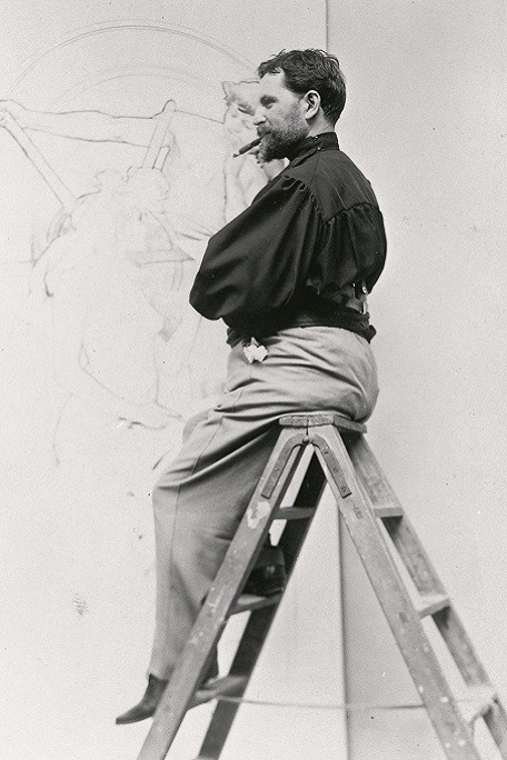 Mucha sitting on the left side of a stepladder in front of a large pencil drawing smoking a cigar and looking out to the left