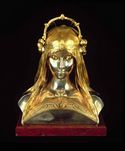 A bust of a young woman with eyes cast downward, an ornamental neckline  and a tall, arched crown with silver lilies on the sides