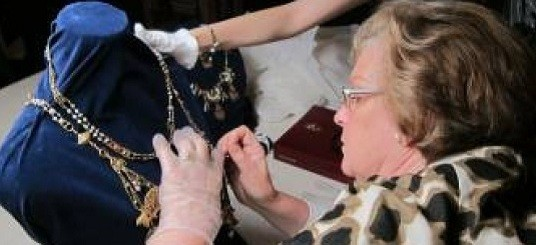 Conservator working on a piece of jewellery assisted by a lady who holds the piece of jewellery in place