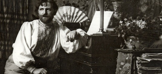 Mucha in his studio dressed in an embroidered smock, seated and leaning on a piece of furniture