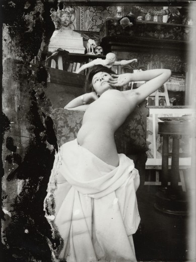Nude female model with a white sheet draped around her lower body leaning back over a chair with her arms raised to shoulder level and her hands to her face