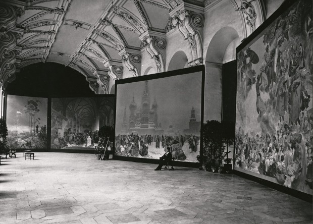 4 canvases are exhibited in a large hall with an ornate cieling and a wooden floor; a man sits on a stool in front of one of the canvases