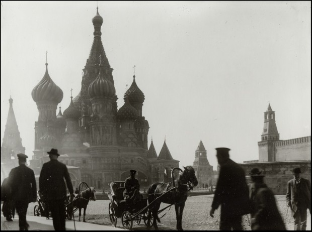 The ornate domes of St Basil's in the background with two horse and carts and several pedestrians in the foreground