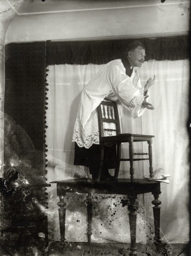 Dressed as a priest, Mucha stands on a table and leans forward over the back of a chair placed on the table