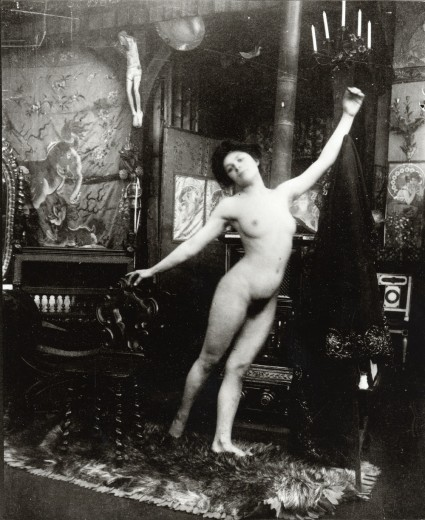 Nude balancing on her left leg holding her right foot just behind her with her arms outstretched leaning up to her left