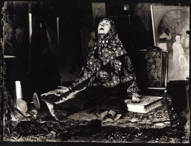 A seated woman with a paterned scarf around her head and shoulders, her legs stretched out in front of her and her arms laid open on the floor sits with her mouth open and her head turned up towards the ceiling