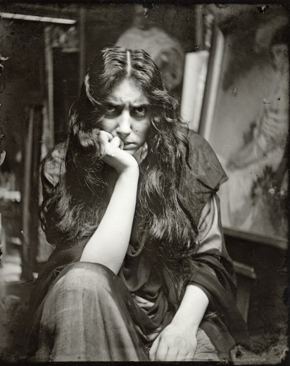A seated female model with bedraggled long, dark hair and an angry expression leans on her knee with her head on her hand