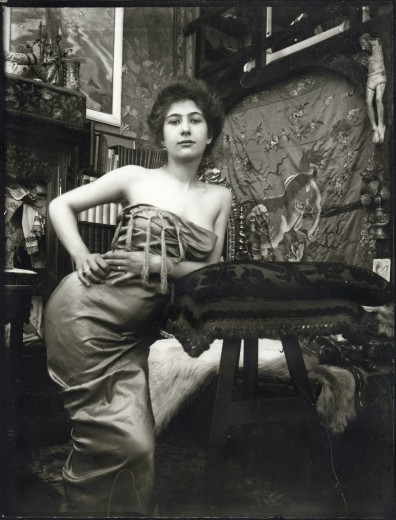 Young bare-shouldered model wrapped in a large piece of fabric leans on a cushion on a pedestal with her left elbow and holds her right hand on her right hip