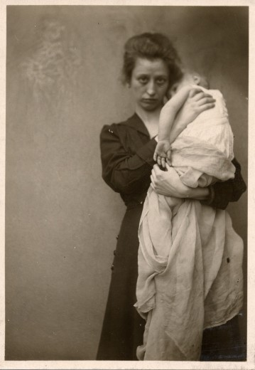 Woman with dark hair and a melancholic expression holds a baby wrapped in a white cloth up to her shoulder
