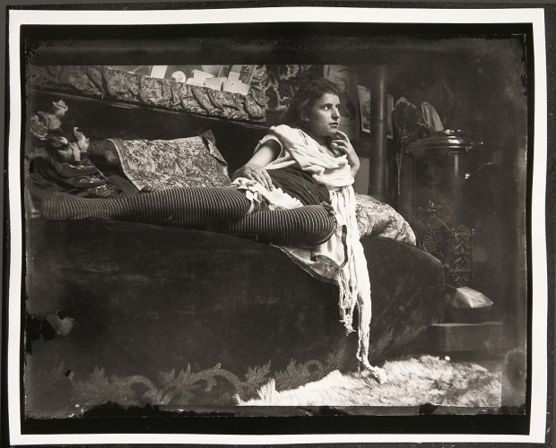 Young woman in stripey stockings with a white scarf around her neck reclining on a velvet couch next to a stove.