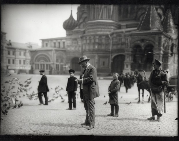 Mucha standing in the middle of the square sketching with boys looking on and St. Basil's cathedral behind