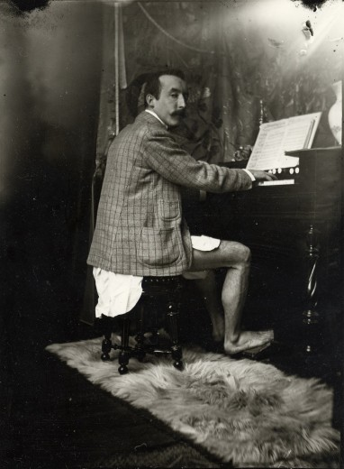 Gauguin sitting at a harmonium wearing only a shirt and jacket, turning towards the camera