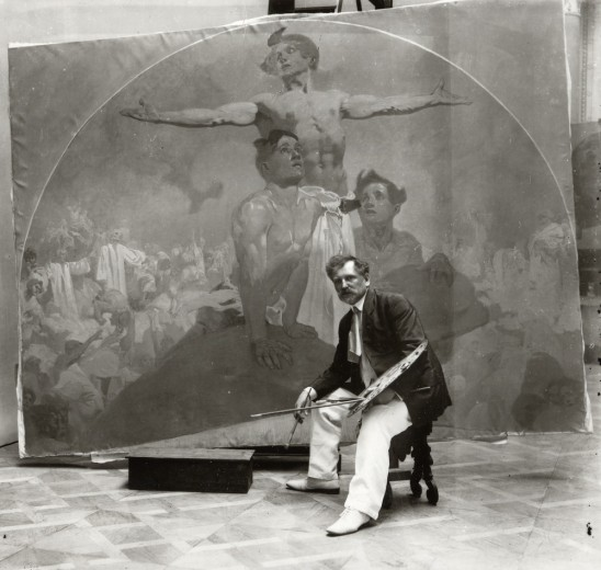 Mucha seated on a stool in front of his mural with a paint palette and paint brush in his hand