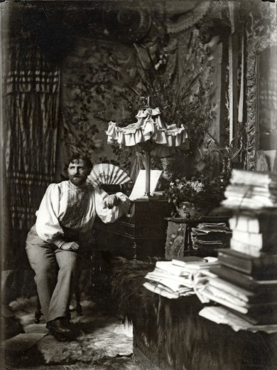 Mucha seated in his studio with ornate fabric in the background, art objects to his right, and piles of books in the foreground